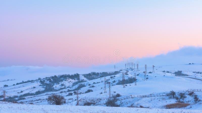 Power poles in a snowy field, winter scene royalty free stock image