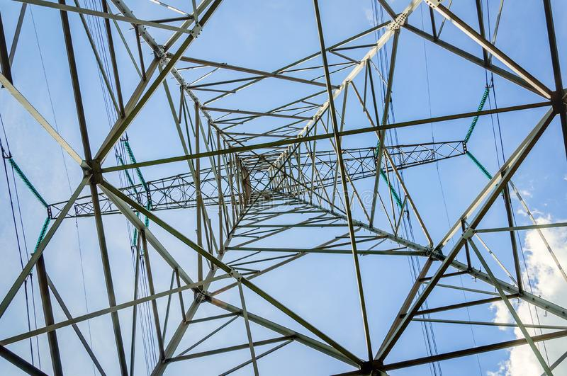 Power pylon from below against a blue sky royalty free stock photo