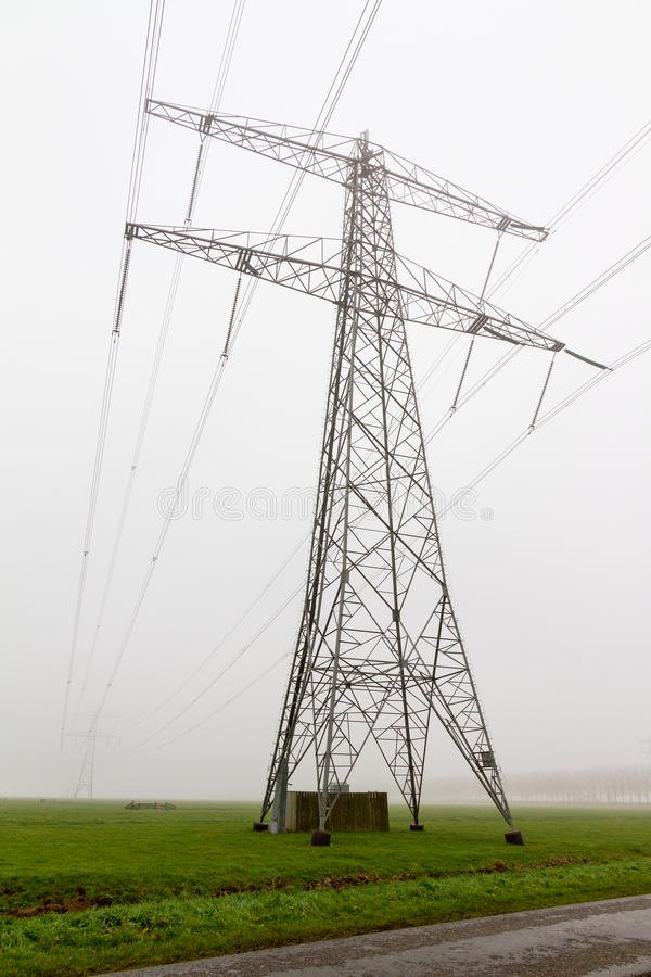 Power pylon mist. Power pylon in a field on a foggy morning in the Netherlands royalty free stock images