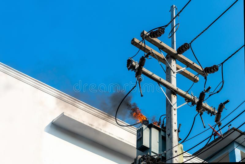 Power pylon overload or electric short circuit at transformer on poles and fire or flame with smoke on blue sky stock image