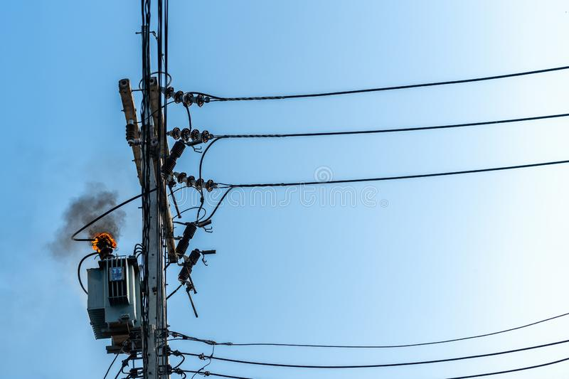 Power pylon overload or electric short circuit at transformer on poles and fire or flame with smoke on blue sky.  stock images