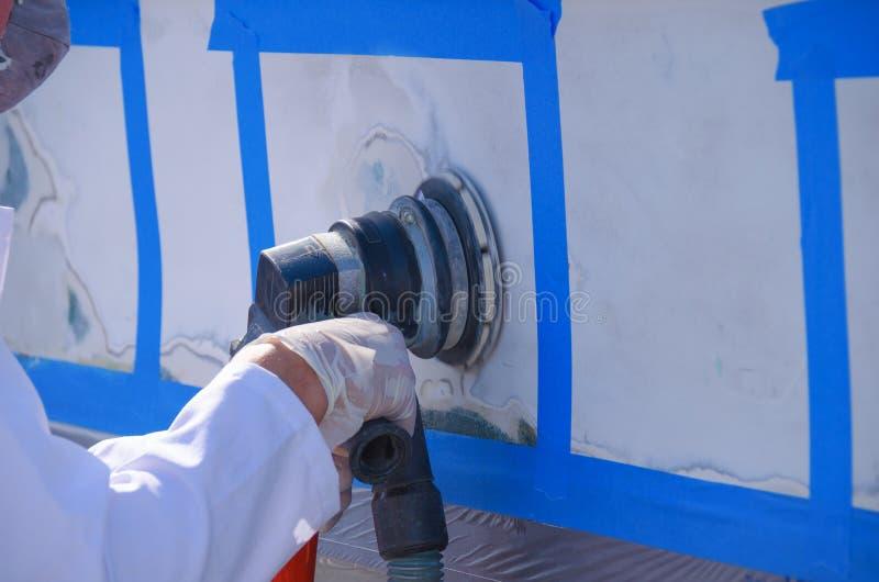 Power sander sanding fiberglass boat hull repair. Closeup of a man sanding a fiberglass boat hull repair area with a power sander that has a vacuum hose stock image