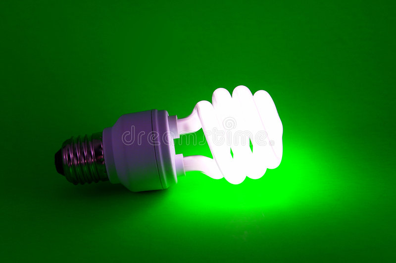 Power-saving light-bulb on green background. A modern power-saving light-bulb lit on green background stock image
