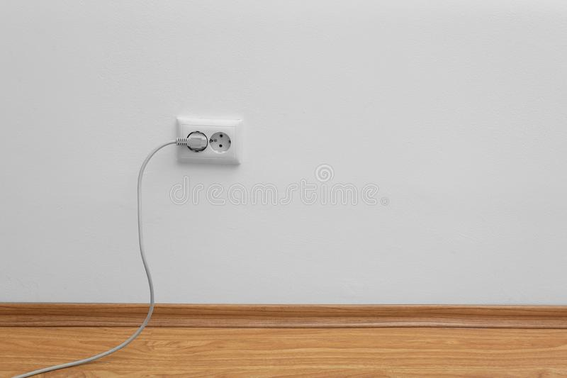 Power socket and plug on wall, space for text. Electrician`s equipment stock images