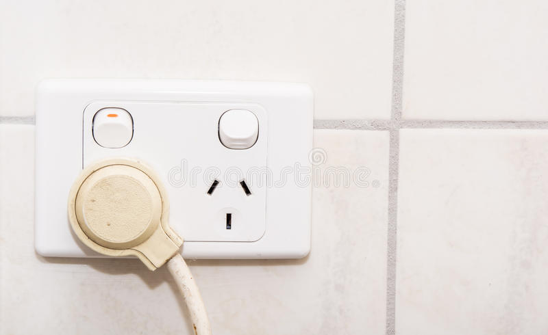 Power socket. White power socket with connection cable on it on the wall of the toilet royalty free stock images