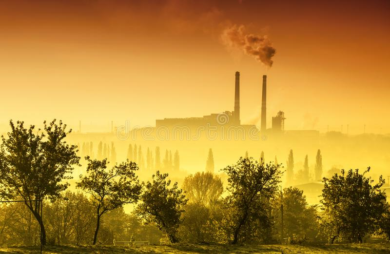 Power station with smoking chimney. At sunset royalty free stock photo