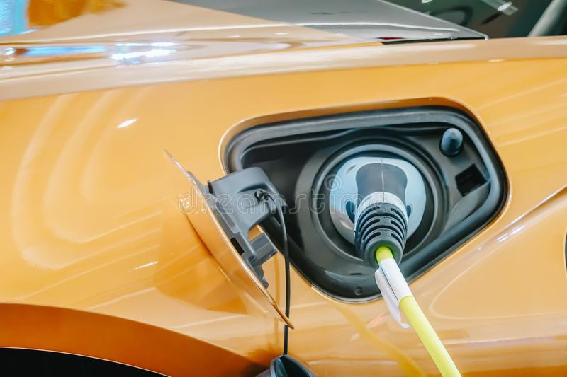 Power supply for electric car charging. Electric car charging station. Close up of the power supply plugged into an electric car stock images
