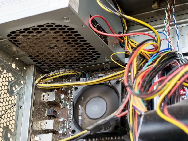 Power supply and wires inside of the personal computer case are covered with dust. A lot of dust under the cooler on the processor stock photos