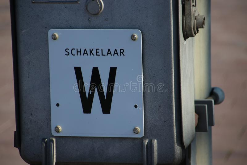 Power switch named W for electricity wires for trains on platform on railroad station Rotterdam Centraal in the Netherlands. royalty free stock photo