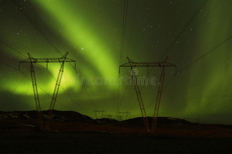 Power to the Northern Lights. Power lines illuminated by the spectacular Aurora Borealis royalty free stock images