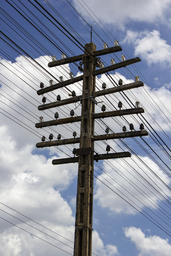 Power tower silhouetted against blue sky stock photography