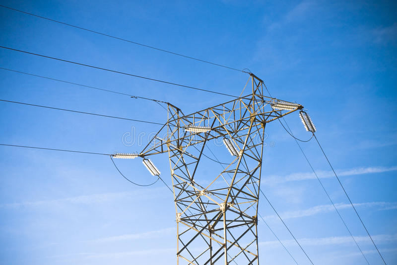 Power tower and transmission lines on blue background stock image