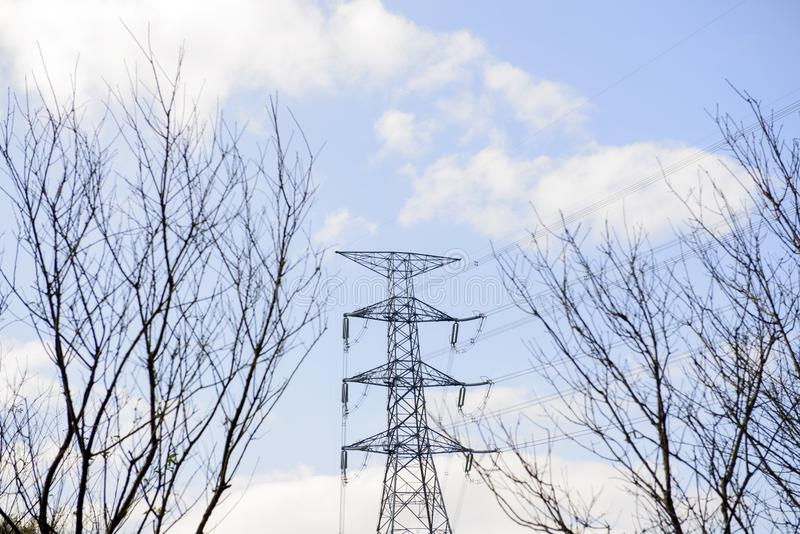 Power tower under a cloudy sky. Electric line with bare tree branch silhouettes stock images