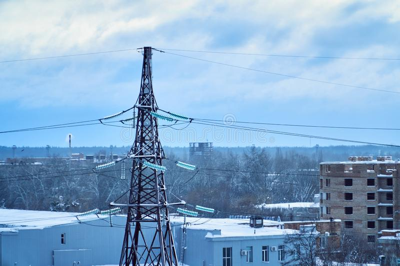 Power transmission line tower against blue sky and clouds with snow-covered high-voltage insulators stock photography