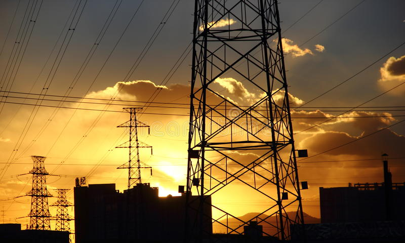 Power transmission line. Towers stand under blue sky with beautiful sunset in the background stock photos