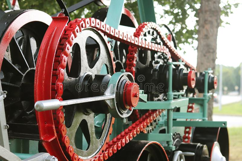 Power unit with wheels, flywheels and chain. Agricultural mechanism for harvest processing. Heavy engineering. Metal construction. Relief of manual labor stock images