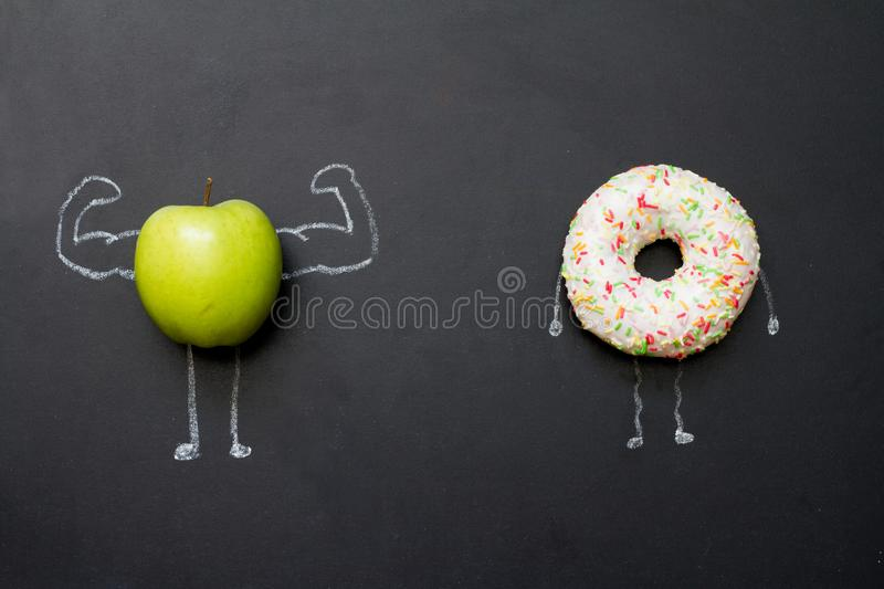 Power of vitamins diet abstract concept with green muscles  apple on blackboard. Xconcept stock photography