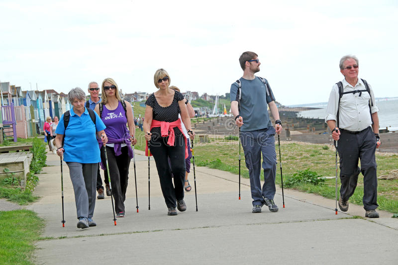 Power walkers. Photo of group power walkers using walking trekking poles along the coast of whitstable in kent england. photo taken 24th may 2015 and ideal for stock photography