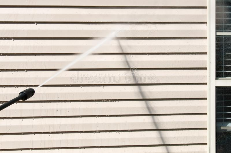 Power washing. House wall siding cleaning with high pressure water jet. royalty free stock photography