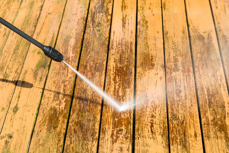 Power washing. Wooden deck floor cleaning with high pressure water jet. stock images