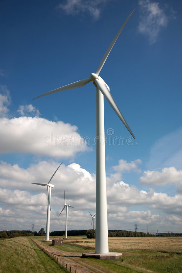 Power Windmills. Row of large white power windmills in the Dutch countryside, with a blue sky background stock photo