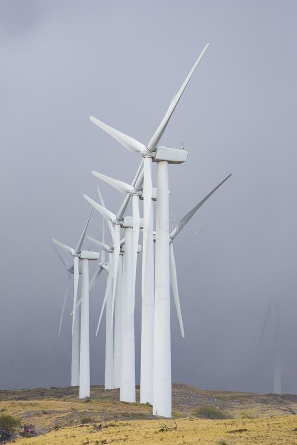 Power windmills on the island of Maui Hawaii. With dark sky background stock photos