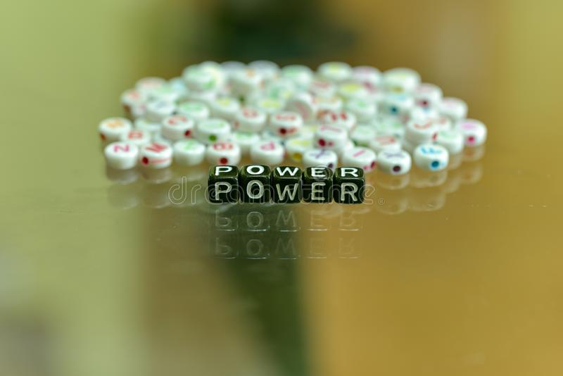 POWER written with Acrylic Black cube with white Alphabet Beads on the Glass Background.  royalty free stock photography