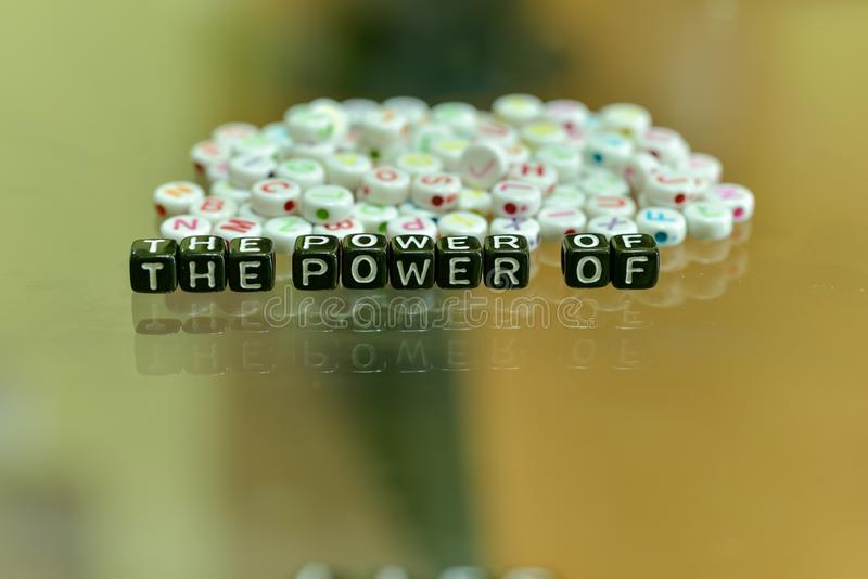 THE POWER OF  written with Acrylic Black cube with white Alphabet Beads on the Glass Background.  royalty free stock photos