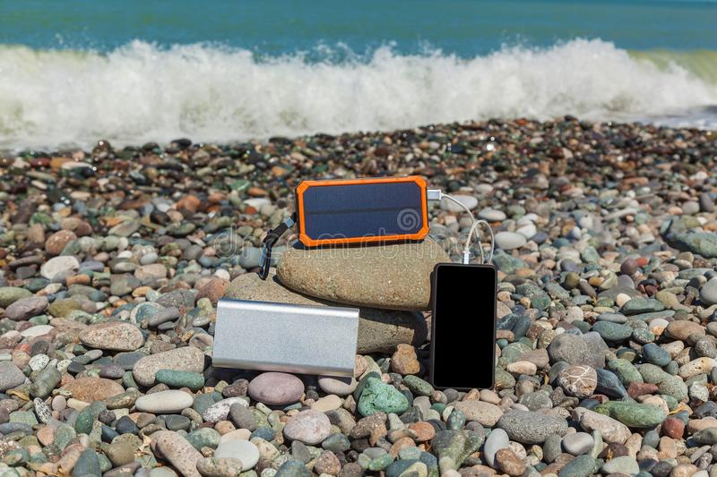 Powerbank charges the phone. The poverbank lies on the pebbles by the sea and charges the phone. Powerbank charges the phone stock image
