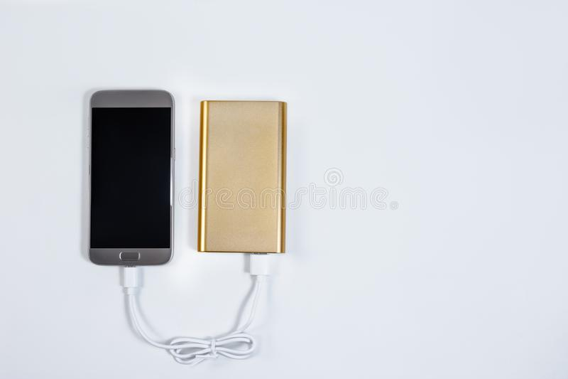 Powerbank d'or avec le téléphone intelligent sur le fond photo stock