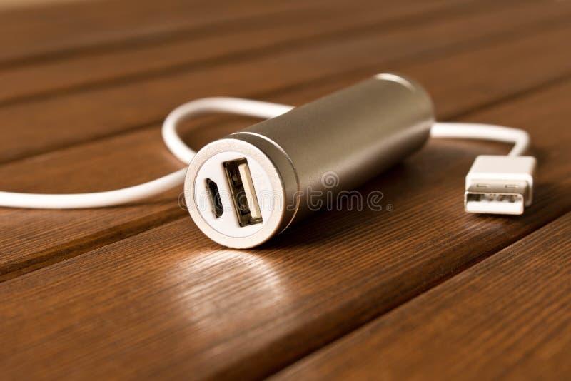 Powerbank de prata com o conector na tabela de madeira foto de stock