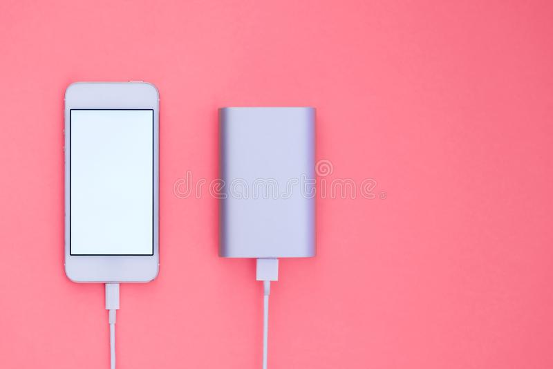Powerbank and phone on pink background. Flat Lay phone layout that charges with Powerbank. Powerbank and phone on orange background. Flat Lay phone layout that stock images