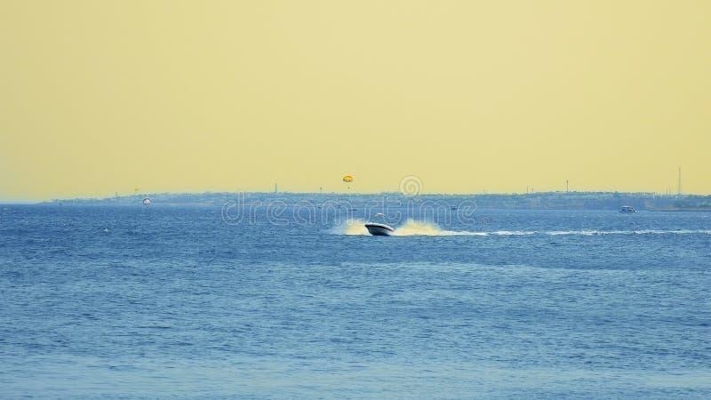 Powerboat ship sails at sunset along tropical sea stock image
