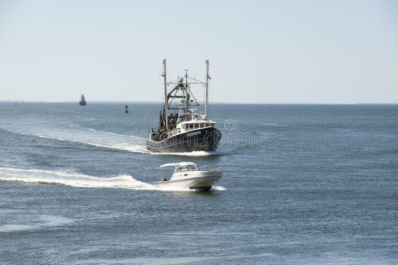 Powerboat som passerar kommersiellt företag för fiska skyttel i New Bedford den yttre hamnen royaltyfri bild