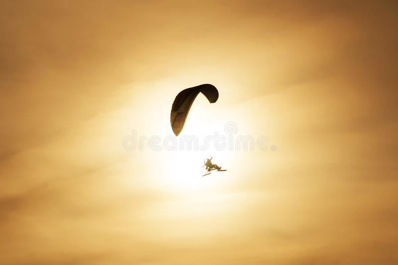 Powered paragliding flying against the backdrop of the setting sun stock photos