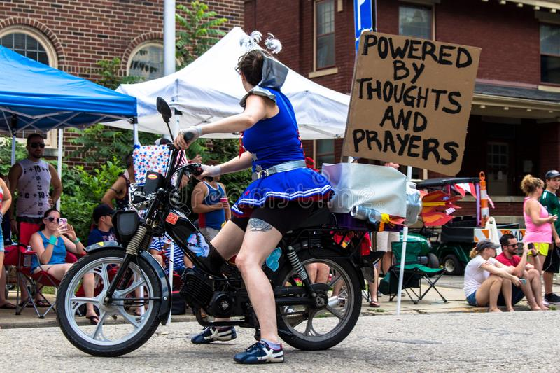 Powered by Thoughts and Prayers. Woman rides motorcycle carrying sign that states `powered by thoughts and prayers.`  Doo Dah satirical political parade in royalty free stock image