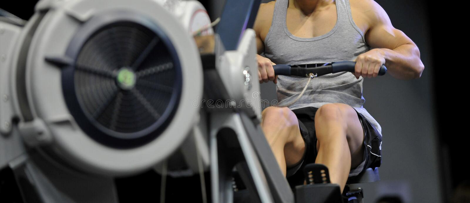 Powerful attractive muscular man CrossFit trainer do workout on indoor rower at the gym.  royalty free stock photo