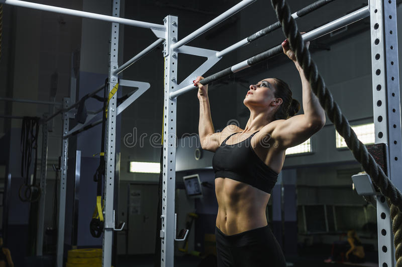 Powerful attractive woman CrossFit trainer do pull ups during workout. Concept: power, strength, healthy lifestyle, sport. Powerful attractive muscular woman stock photo
