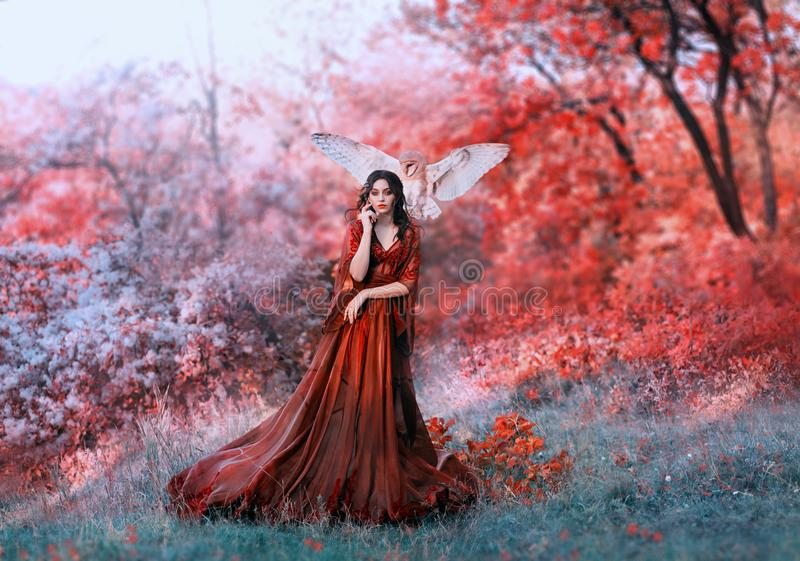 Powerful autumn nymph, queen of fire and goddess of hot sun, lady in long red light dress with loose sleeves with dark. Hair, model in scarlet forest with royalty free stock photography
