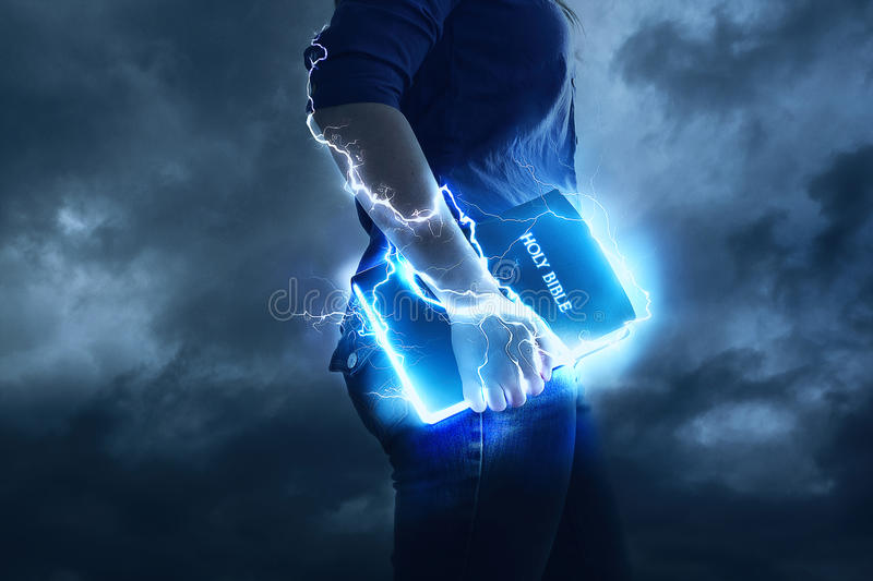 Powerful Bible. A woman holds her Bible with glowing lights and lightning strikes