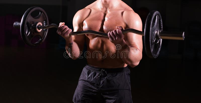 Close up of bodybuilder doing the exercises with barbell. Strong male with naked torso on dark background. Strength and royalty free stock images