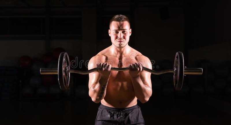 Powerful bodybuilder doing the exercises with barbell. Strong male with naked torso on dark background. Strength and royalty free stock images