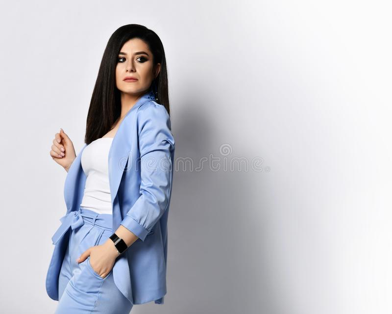 Powerful business woman in blue official suit turned back and looked over her shoulder at free text space on white royalty free stock images