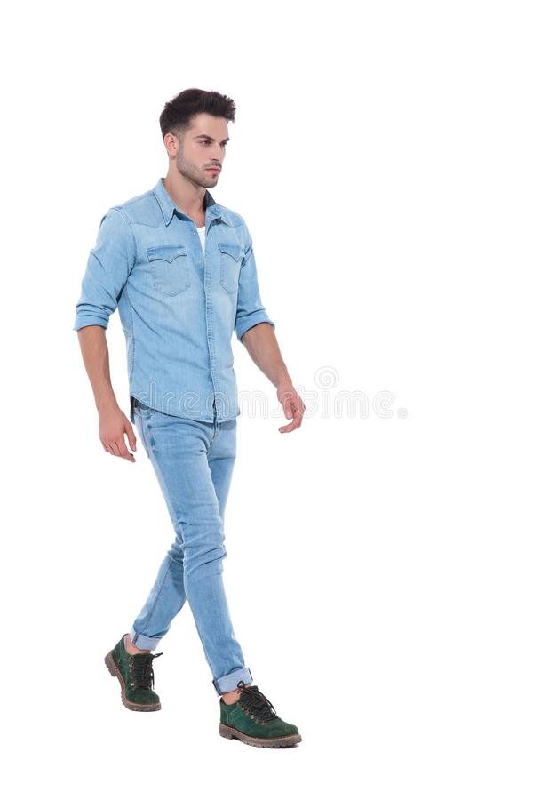 Powerful and confident man wearing denim and walking stock images