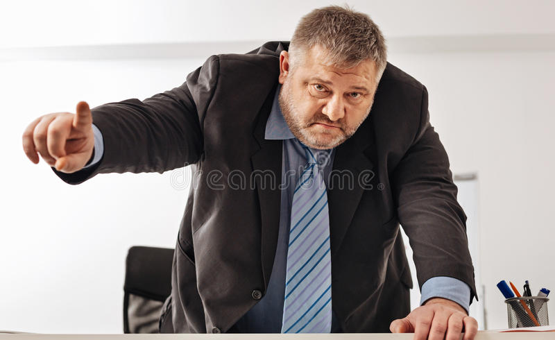 Powerful corpulent businessman threatening someone. If any objections door is that way. Professional distressed office manager telling about punishing his stock photo