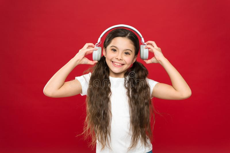Powerful effect music teenagers their emotions, perception of world. Girl listen music headphones on red background. Modern gadget concept. Music taste. Music stock image