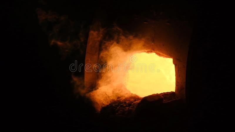 Powerful flame of industrial fire at plant. Stock footage. From factory furnace burst with pressure of strong jets of. Orange flame. Bucket of fire for smelting royalty free stock image