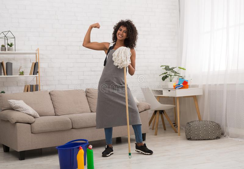 Powerful housewife holding mop and showing biceps royalty free stock photo