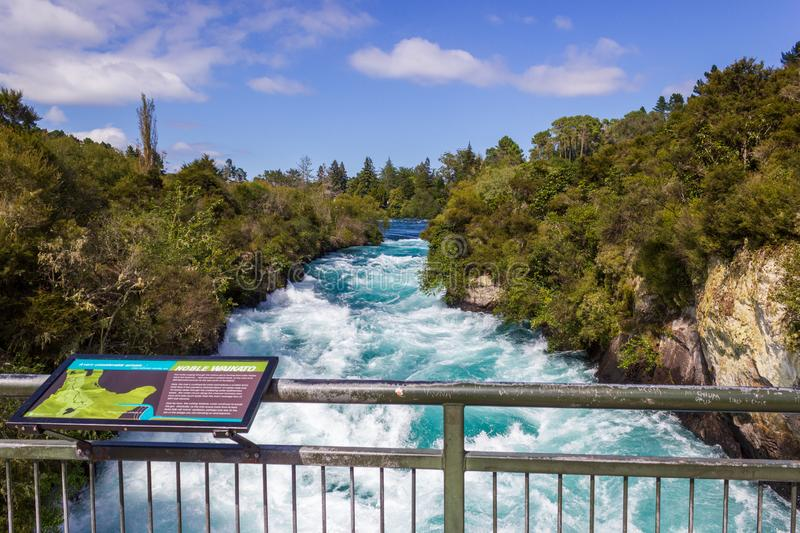 Powerful Huka Falls with a sign with information about the falls, on the Waikato River near Taupo North Island New Zealand. Powerful Huka Falls on the Waikato royalty free stock photo