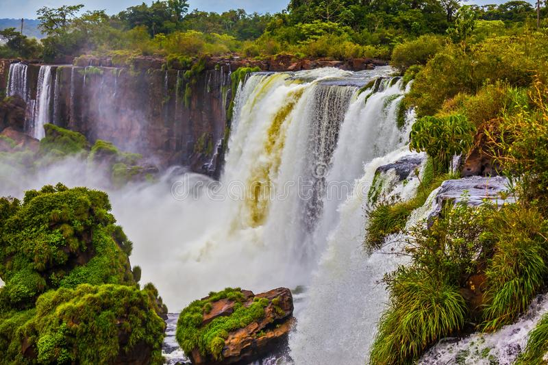 Powerful jets of water. Travel to Argentina. The concept of exotic and active tourism. Powerful jets of the world famous waterfalls Iguazu. Picturesque basaltic royalty free stock photo